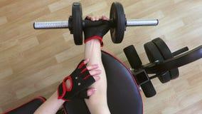 Vrouw die in gymnastiek geschiktheidsoefeningen met domoren voor voorarmen doen stock videobeelden