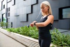 Vrouw die haar apparaat van het geschiktheids slim horloge in stedelijk milieu controleren stock foto