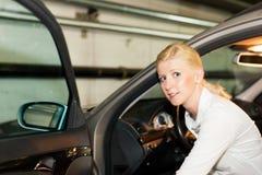 Vrouw die in haar auto krijgt Royalty-vrije Stock Foto's