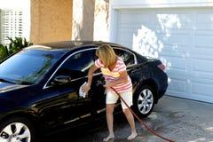 Vrouw die haar auto schoonmaakt Royalty-vrije Stock Afbeelding
