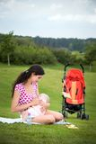 Vrouw die haar baby in openlucht de borst geven Stock Afbeeldingen