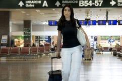 Vrouw die haar bagage in luchthaven brengt Stock Fotografie