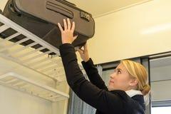Vrouw die haar bagage op treinrek zetten Stock Foto's