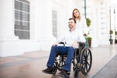 Vrouw die haar boyfriend& x27 duwen; s rolstoel royalty-vrije stock afbeelding