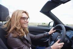 Vrouw die haar cabriolet sportwagen drijven royalty-vrije stock afbeelding