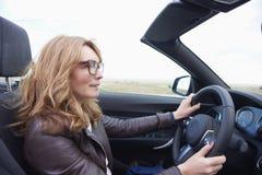 Vrouw die haar cabriolet sportwagen drijven stock foto