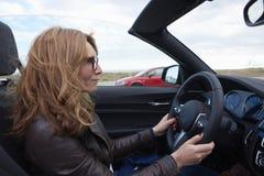 Vrouw die haar cabriolet sportwagen drijven stock afbeeldingen