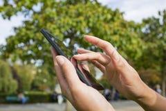 Vrouw die haar celtelefoon in een park met behulp van Stock Fotografie