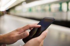 Vrouw die haar celtelefoon op metroplatform met behulp van Royalty-vrije Stock Foto's