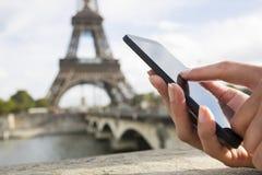 Vrouw die haar celtelefoon voor de Toren van Eiffel met behulp van Royalty-vrije Stock Afbeelding