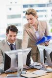 Vrouw die haar collega iets op het scherm tonen Stock Foto's