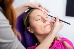 Vrouw die Haar die Make-up hebben in Salon wordt toegepast royalty-vrije stock foto's