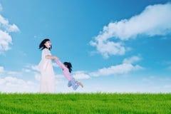 Vrouw die haar dochter spinnen bij gebied Stock Foto's