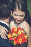 Vrouw die haar echtgenoot met boeket in handen omhelzen Stock Foto