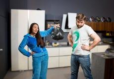 Vrouw die haar echtgenoot vragen om het afval te nemen Stock Afbeelding