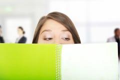 Vrouw die haar gezicht achter een notitieboekje verbergen Stock Afbeelding