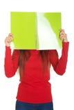 Vrouw die haar gezicht achter een notitieboekje verbergen Stock Afbeeldingen