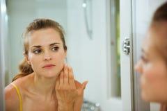 Vrouw die haar gezicht in spiegel in badkamers controleert Stock Afbeelding