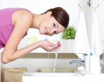 Vrouw die haar gezicht wast door water Stock Afbeeldingen