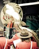 Vrouw die haar gouden heldere tuba in de straat spelen stock fotografie