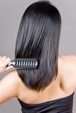 Vrouw die Haar Haar borstelt Stock Foto's