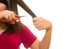 Vrouw die haar haar met schaar snijden - ongelukkige uitdrukking, isola Stock Foto