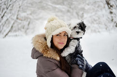 Vrouw die haar hond in het de winterbos koesteren Stock Afbeeldingen