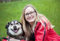 Vrouw die haar hond koesteren stock fotografie