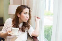 Vrouw die haar koffiekop houden Royalty-vrije Stock Afbeeldingen