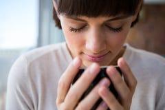 Vrouw die haar kop van koffie met haar gesloten ogen ruiken stock foto's