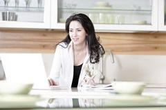Vrouw die haar laptop in keuken met behulp van Royalty-vrije Stock Foto's