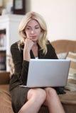 Vrouw die in haar laptop werkt Stock Foto