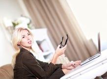 Vrouw die in haar laptop werkt Stock Foto's