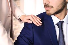 Vrouw die haar mannelijke collega in bureau, close-up lastig vallen stock foto