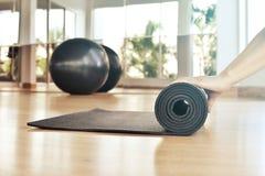 Vrouw die haar mat na een yogaklasse rollen Stock Foto's