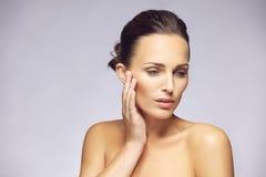 Vrouw die haar mooie huid strelen Stock Afbeelding