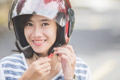 Vrouw die haar motorhelm vastmaken stock afbeelding