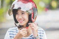 Vrouw die haar motorhelm vastmaken stock foto's
