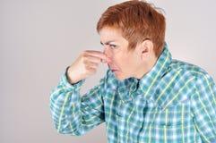 Vrouw die haar neus met haar vingers houden Stock Foto's
