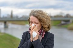 Vrouw die haar neus op een weefsel in openlucht blazen royalty-vrije stock afbeeldingen