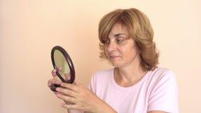 Vrouw die haar nieuw kapsel in de spiegel bekijken stock video
