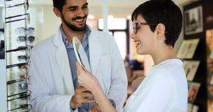 Vrouw die haar nieuwe glazen kiezen bij opticaopslag met hulp van oftalmoloog stock afbeeldingen