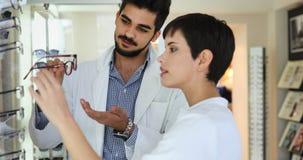 Vrouw die haar nieuwe glazen kiezen bij opticaopslag met hulp van oftalmoloog stock foto's