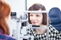 vrouw die haar ogen heeft die door een oogarts worden onderzocht stock afbeelding