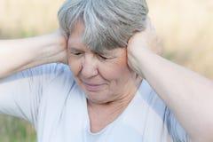 Vrouw die haar oren gesloten houden Stock Afbeelding
