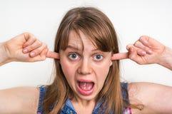 Vrouw die haar oren tegen hevig lawaai behandelen te beschermen stock fotografie