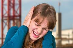Vrouw die haar oren tegen hevig lawaai behandelen te beschermen royalty-vrije stock afbeelding
