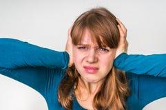 Vrouw die haar oren tegen hevig lawaai behandelen te beschermen stock foto