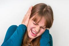 Vrouw die haar oren tegen hevig lawaai behandelen te beschermen stock afbeeldingen