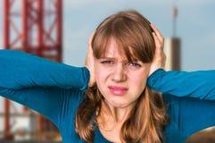 Vrouw die haar oren tegen hevig lawaai behandelen te beschermen royalty-vrije stock afbeeldingen